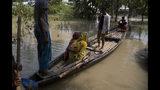 En esta imagen del viernes 19 de julio de 2019, Imrana Khatoon, vestida de amarillo, sale de su casa en un bote para llegar a un hospital, mientras una mujer a su lado sostiene a su bebé recién nacido en Gagalmari, una zona afectada por las inundaciones al este de Gauhati, India. (AP Foto/Anupam Nath)