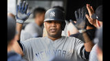 New York Yankees' Edwin Encarnacion celebrates in the Yankee dugout after scoring on a double by teammate Didi Gregorius against the Minnesota Twins in the first inning of a baseball game, Tuesday, July 23, 2019, in Minneapolis. (AP Photo/Tom Olmscheid)