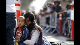 FILE - In this July 16, 2019 file photo, a woman sits with her sons as they wait to apply for asylum in the United States along the border in Tijuana, Mexico. The American Civil Liberties Union said Tuesday, July 30, 2019 that more than 900 children have been separated from their families at the border since a judge ordered last year that the practice be sharply curtailed. The ACLU says about one of every five children separated is under 5 years old. (AP Photo/Gregory Bull, File)