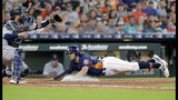 Seattle Mariners catcher Omar Narvaez, left, waits for the ball as Houston Astros' Jake Marisnick, right, dives safely for the plate on the sacrifice fly by Josh Reddick during the seventh inning of a baseball game Sunday, Aug. 4, 2019, in Houston. (AP Photo/Michael Wyke)