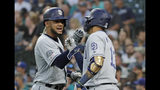 San Diego Padres' Fernando Tatis Jr., left, is greeted by Manny Machado, right, after Tatis Jr. hit a two-run home run during the fifth inning of the team's baseball game against the Seattle Mariners, Tuesday, Aug. 6, 2019, in Seattle. (AP Photo/Ted S. Warren)