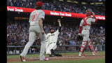 San Francisco Giants' Brandon Belt, bottom, slides into home plate to score a run between Philadelphia Phillies pitcher Aaron Nola (27) and catcher Andrew Knapp during the third inning of a baseball game in San Francisco, Thursday, Aug. 8, 2019. (AP Photo/Jeff Chiu)