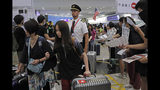 Passengers and flight crew arrive at Hong Kong International Airport, Monday, Aug. 12, 2019. One of the world's busiest airports canceled all flights after thousands of Hong Kong pro-democracy protesters crowded into the main terminal Monday afternoon. (AP Photo/Kin Cheung)