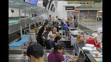 Stranded travelers sit in the check-in counters at the Hong Kong International Airport, Monday, Aug. 12, 2019. One of the world's busiest airports canceled all flights after thousands of Hong Kong pro-democracy protesters crowded into the main terminal Monday afternoon. (AP Photo/Kin Cheung)