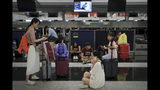 Travelers gather at the closed check-in counters as protesters stage a protest at the Hong Kong International Airport, Monday, Aug. 12, 2019. One of the world's busiest airports canceled all flights after thousands of Hong Kong pro-democracy protesters crowded into the main terminal Monday afternoon. (AP Photo/Kin Cheung)