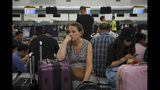 Australian Penny Tilley, center, reacts next to stranded travelers at the closed check-in counters at the Hong Kong International Airport, Monday, Aug. 12, 2019. One of the world's busiest airports canceled all flights after thousands of Hong Kong pro-democracy protesters crowded into the main terminal Monday afternoon. (AP Photo/Kin Cheung)