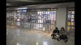 Passengers sit near a closed duty free shop at the Hong Kong International airport, Monday, Aug. 12, 2019. One of the world's busiest airports cancelled all remaining departing and arriving flights after thousands of Hong Kong pro-democracy protesters crowded into the main terminal. (AP Photo/Vincent Thian)