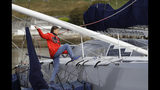 Greta Thunberg climbs onto the boat Malizia as it is moored in Plymouth, England Tuesday, Aug. 13, 2019. Greta Thunberg, the 16-year-old climate change activist who has inspired student protests around the world, is heading to the United States this week - in a sailboat. (AP Photo/Kirsty Wigglesworth)