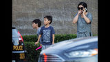 A woman and her two children stand near the scene where a shootout near a freeway killed a California Highway Patrol officer and wounded two others before the gunman was fatally shot, Monday, Aug. 12, 2019, in Riverside, Calif. (Terry Pierson/The Orange County Register via AP)