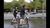 Dos jóvenes operan patinetas eléctricas en París el 12 de agosto del 2019. Las autoridades de las ciudades europeas se afanan por regular el uso de estos vehículos, que están invadiendo las urbes de todo el mundo. (AP Photo/Lewis Joly)