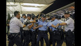 Policemen pull back after reacting with protesters outside the Airport in Hong Kong, Tuesday, Aug. 13, 2019. Riot police clashed with pro-democracy protesters at Hong Kong's airport late Tuesday night, a chaotic end to a second day of demonstrations that caused mass flight cancellations at the Chinese city's busy transport hub. (AP Photo/Vincent Yu)