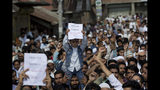 A Kashmiri Muslim boy holds a placard as others shout slogans during a protest after Eid prayers in Srinagar, Indian controlled Kashmir, Monday, Aug. 12, 2019. Troops in India-administered Kashmir allowed some Muslims to walk to local mosques alone or in pairs to pray for the Eid al-Adha festival on Monday during an unprecedented security lockdown that still forced most people in the disputed region to stay indoors on the Islamic holy day. (AP Photo/ Dar Yasin)