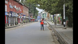 A civic worker cleans a deserted street during a security lockdown in Srinagar, Indian controlled Kashmir, Monday, Aug. 12, 2019. Troops in India-administered Kashmir allowed some Muslims to walk to local mosques alone or in pairs to pray for the Eid al-Adha festival on Monday during an unprecedented security lockdown that still forced most people in the disputed region to stay indoors on the Islamic holy day. (AP Photo/Mukhtar Khan)