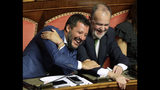 Italian Interior Minister and Deputy-Premier Matteo Salvini, left, laughs as he sits beside The League party's Roberto Calderoli, at the Senate in Rome, Tuesday, Aug. 13, 2019. Italy's political leaders scrambled to line up allies and form alliances Tuesday as the country's right-wing interior minister pressed his demands for an early election in the hope of snagging the premiership as a platform for his anti-migrant, euroskeptic agenda. Senators hastily summoned back from a vacation break convened for a vote on scheduling their consideration of a no-confidence motion lodged by Matteo Salvini's League party against Premier Giuseppe Conte's 14-month-old populist government. (AP Photo/Alberto Pellaschiar)