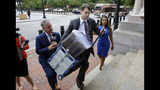Nathan Carman, center, carries documents as he arrives at federal court, Tuesday, Aug. 13, 2019, in Providence, R.I. Carman faces civil charges in federal court over insurance issues regarding the boat aboard which he and his mother went out to sea for a night of fishing in 2016. The boat sank, Carman survived but his mother was never found. (AP Photo/Steven Senne)