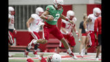In this photo taken Aug. 7, 2019, Nebraska quarterback Adrian Martinez (2) leaps over a player during NCAA college football preseason practice in Lincoln, Neb. Martinez, the most productive freshman quarterback in the nation last season, averaged 371 yards of total offense against West Division opponents and 295 overall. He led an offense that ranked second in the Big Ten and scored 30 points per game. (AP Photo/Nati Harnik)