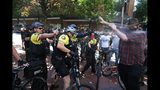 FILE - In this June 29, 2019, file photo, after a confrontation between authorities and protesters, police use pepper spray as multiple groups, including Rose City Antifa, the Proud Boys and others protest in downtown Portland, Ore. Portland police are mobilizing in hopes of avoiding clashes between out-of-state hate groups planning a rally Saturday, Aug. 17, 2019, and homegrown anti-fascists who say they'll come out to oppose them. (Dave Killen/The Oregonian via AP, File)