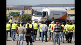 Tanker truck drivers on strike watch a fellow driver leaving a fuel depot in Aveiras, outside Lisbon, Monday, Aug. 12, 2019. Portugal is rationing gas as a precaution after some 2,000 tanker truck drivers began an open-ended strike over pay on Monday. (AP Photo/Armando Franca)