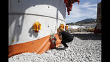 A relative of one of the victims leaves flowers on one of the pillars of the new bridge being built, during a remembrance ceremony to mark the first anniversary of the Morandi bridge collapse, in Genoa, Italy, Wednesday, Aug. 14, 2019. The Morandi bridge was a road viaduct on the A10 motorway in Genoa, that collapsed one year ago killing 43 people. (AP Photo/Antonio Calanni)