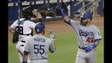 El jugador de los Dodgers de Los Ángeles, el puertorriqueño Edwin Ríos (43), celebra tras conectar su jonrón solitario, mientras su compañero Russell Martin (55) lo espera en el plato durante el cuarto inning de un juego de bíesbol contra los Marlins de Miami, el miércoles 14 de agosto de 2019, en Miami. (AP Foto/Lynne Sladky)