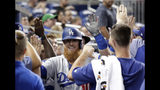 Los Angeles Dodgers' Justin Turner is congratulated in the dugout after hitting a two-run during the seventh inning of a baseball game against the Miami Marlins, Tuesday, Aug. 13, 2019, in Miami. (AP Photo/Lynne Sladky)