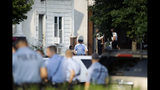 Authorities stand outside a house as they investigate an active shooting situation, Wednesday, Aug. 14, 2019, in the Nicetown neighborhood of Philadelphia. (AP Photo/Matt Rourke)