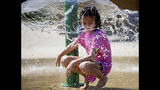 Abigail Sisney, 8, cools down from the hot weather in the splash pad at Rayola Park in Owasso, Okla., Monday, Aug. 12, 2019. (Mike Simons/Tulsa World/Tulsa World via AP)