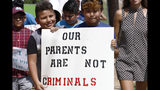FILE - In this Aug. 11, 2019, file photo, children of mainly Latino immigrant parents hold signs in support of them and those individuals picked up during an immigration raid at a food processing plant, during a protest march to the Madison County Courthouse in Canton, Miss. Unauthorized workers are jailed or deported, while the managers and business owners who profit from their labor often aren't. Under President Donald Trump, the numbers of owners and managers facing criminal charges for employing unauthorized workers have stayed almost the same. (AP Photo/Rogelio V. Solis, File)