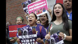 Protesters display placards and chant slogans, Wednesday, Aug. 14, 2019, while gathered outside federal court, in Boston. The demonstration was held to protest the Trump administration's campaign to end temporary protected status, or TPS, for tens of thousands of immigrants nationwide. (AP Photo/Steven Senne)