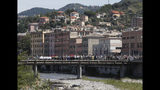 People that did not take part in the ceremony to mark the first anniversary of the Morandi bridge collapse, stage their own commemoration on the bridge on the Polcevera river in Genoa, Italy, Wednesday, Aug. 14, 2019. The Morandi bridge was a road viaduct on the A10 motorway in Genoa, that collapsed one year ago killing 43 people. (AP Photo/Antonio Calanni)