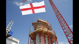 The flag of Genoa flies next to one of the new pillars being built, during a remembrance ceremony to mark the first anniversary of the Morandi bridge collapse, in Genoa, Italy, Wednesday, Aug. 14, 2019. The Morandi bridge was a road viaduct on the A10 motorway in Genoa, that collapsed one year ago killing 43 people. (AP Photo/Antonio Calanni)