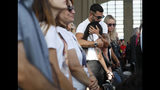 Relatives of the victims of the Morandi bridge collapse, embrace during a remembrance ceremony to mark the first anniversary of the tragedy, in Genoa, Italy, Wednesday, Aug. 14, 2019. The Morandi bridge was a road viaduct on the A10 motorway in Genoa, that collapsed one year ago killing 43 people. (AP Photo/Antonio Calanni)