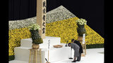 Japanese Emperor Naruhito, accompanied by Empress Masako bows before the main altar decorated with huge bank of chrysanthemums during a memorial service at Nippon Budokan Martial Arts Hall in Tokyo Thursday, Aug. 15, 2019. Japan marked Thursday the 74th anniversary of the end of World War II. (AP Photo/Eugene Hoshiko)
