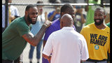 LeBron James laughs with coach Dru Joyce and former teammates before playing I Promise School students in a game of basketball during the debut of the new basketball court at I Promise School, Wednesday, Aug. 14, 2019, in Akron, Ohio. (Jeff Lange/Akron Beacon Journal via AP)