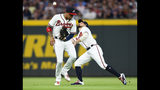 Atlanta Braves shortstop Johan Camargo moves away from a ball hit by New York Mets' Pete Alonso as center fielder Ender Inciarte, right, makes the catch during the first inning of a baseball game Wednesday, Aug. 14, 2019, in Atlanta. (AP Photo/John Amis)
