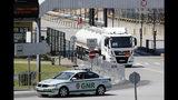 Un auto policial escolta a un camión cisterna a la salida de un depósito de combustible en Aveiras, a las afueras de Lisboa, el martes 13 de agosto de 2019. (AP Foto/Armando Franca)