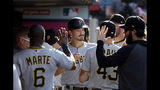 Pittsburgh Pirates' Bryan Reynolds, center, is greeted in the dugout after scoring on a single from Melky Cabrera during the first inning of the team's baseball game against the Los Angeles Angels on Wednesday, Aug. 14, 2019, in Anaheim, Calif. (AP Photo/Marcio Jose Sanchez)