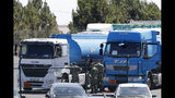 Soldiers get ready two tanker trucks at a fuel depot in Aveiras, outside Lisbon, Tuesday, Aug. 13, 2019. Soldiers are driving tanker trucks to distribute gas in Portugal as an open-ended truckers' strike over pay enters its second day. The government has issued an order allowing the army to be used. (AP Photo/Armando Franca)