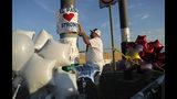"""En esta foto de archivo del 6 de agosto de 2019, un hombre coloca un cartel de """"El Paso Strong"""" (Fuerza El Paso) en un monumento improvisado a las víctimas de la masacre de El Paso, Texas. (AP Foto/John Locher, Archivo)"""