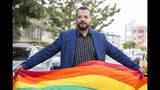 El activista LGBT Mounir Baatour sostiene una bandera multicolor gay tras presentar su solicitud para ser candidato presidencial en la elección anticipada de septiembre, en Túnez, Túnez, el jueves 8 de agosto del 2019. (AP Foto/Hassene Dridi)