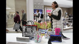 FILE - In this March 14, 2019 file photo a woman shops at Neiman Marcus during the opening night of The Shops & Restaurants at Hudson Yards in New York. Retailers and consumer product makers like American Textile may have received some short moment of reprieve after the Trump Administration delayed the 10% tariffs on some products which also include toys, clothing and shoes. (AP Photo/Mark Lennihan, File)