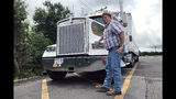 In this June 13, 2019 photo, truck driver Terry Button poses with his truck during at stop in Opal, Va., Thursday, June 13, 2019. The Trump administration has moved a step closer to relaxing federal regulations governing the amount of time truck drivers can spend behind the wheel. (AP Photo/Tom Sampson)