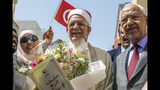 First Vice President of the Assembly Abdelfattah Mourou, center, and Tunisia's Islamist Ennahda party leader Rachid Ghannouchi, right, pose for pictures after Mourou submitted his candidacy for the presidential elections in Tunis, Tunisia, Friday, Aug. 9, 2019. (AP Photo/Hassene Dridi)