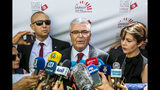 Tunisian Defense Minister Abdelkrim Zbidi speaks to members of the media after submitting his candidacy for the upcoming early presidential elections in Tunis, Tunisia. Wednesday, Aug. 7, 2019. (AP Photo/Hassene Dridi)