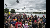 """Members of the Proud Boys and other right-wing demonstrators march along the Willamette River during an """"End Domestic Terrorism"""" rally in Portland, Ore., on Saturday, Aug. 17, 2019. Police have mobilized to prevent clashes between conservative groups and counter-protesters who converged on the city. (AP Photo/Noah Berger)"""