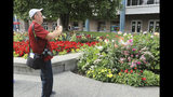 Central Florida resident Paul Leake photographs a dahlia garden in Town Square in Anchorage, Alaska, Thursday, Aug. 15, 2019. Alaska recorded its warmest month ever in July and hot, dry weather has continued in Anchorage and much of the region south of the Alaska Range. (AP Photo/Dan Joling)