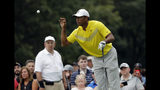 Tiger Woods catches the ball from his caddie, Joe LaCava on the 12th hole during the third round of the BMW Championship golf tournament at Medinah Country Club, Saturday, Aug. 17, 2019, in Medinah, Ill. (AP Photo/Nam Y. Huh)