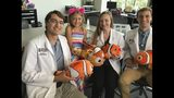This Aug. 8, 2019 photo shows Lily Larimer, flanked by University of South Carolina School of Medicine Greenville medical students Dan Strat, Rikki Williams and Tanner Karp in Greenville, S.C. Lily was born with a limb deficiency of her right hand So when the Simpsonville family saw a notice about a program that offers 3D printed limbs to children, they signed her up. (Liv Osby/The Greenville News via AP)