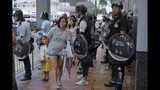 A woman with a child walks past police officers at a police station during a march by pro-democracy protesters in Hong Kong Saturday, Aug. 17, 2019. Another weekend of protests is underway in Hong Kong as Mainland Chinese police are holding drills in nearby Shenzhen, prompting speculation they could be sent in to suppress the protests. (AP Photo/Kin Cheung)
