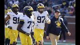 """FILE- In an April 13, 2019, file photo, Michigan head coach Jim Harbaugh walks out with players during the team's annual spring NCAA college football game in Ann Arbor, Mich. Harbaugh seems to be set up for success at Michigan in his fifth season, leading a program that is a popular choice to win the Big Ten. """"That's where I would pick us,"""" Harbaugh said. Some are predicting the Wolverines will earn a spot in the College Football Playoff to give them a chance to win a national championship for the first time since 1997. (AP Photo/Carlos Osorio, File)"""